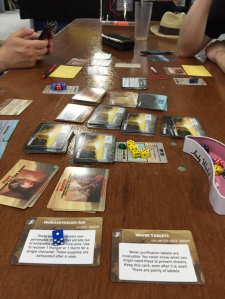 Play testing the War Zone Hope Inhumanity expansion cards at CanGames 2015.